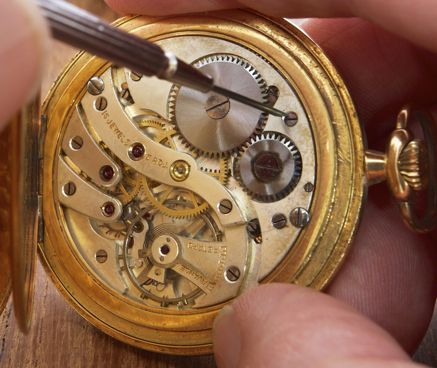 hands that repair an old pocket watch